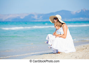 Young mother with her son on beach vacation