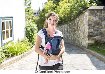 Young mother with her toddler child in a baby carrier