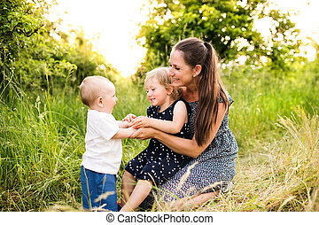Young mother with little children in sunny summer nature