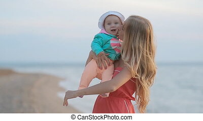 Young mother with long blond hair holding baby in her arms while standing near the sea