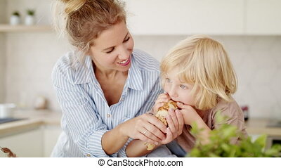 Young mother with small boy indoors in kitchen, eating pancakes.