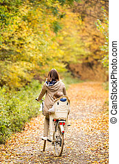 Young mother with son cycling in autumn park - Beautiful...
