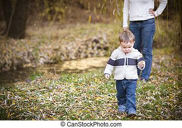 Young mother with son in autumn park