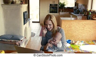Young mother with son in the arms, making phone call.