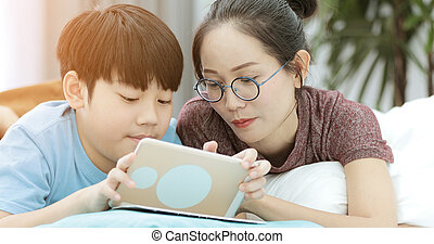 Young mother with son playing with a smartphone on a bed.