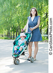 mother with stroller - young mother with stroller is walking...