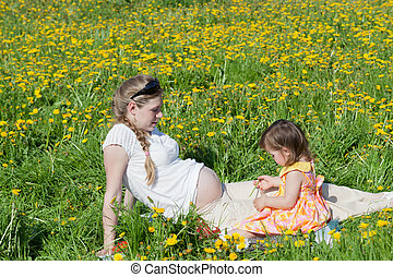 Young mother with the small daughter on summer walk