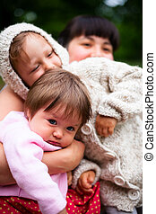 young mother with two daughters playing outdoors