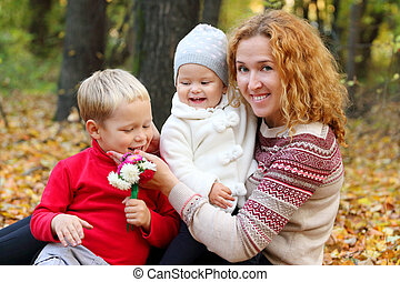 Young mother with two happy children with flowers in autumn forest
