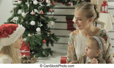 Young mother with two lovely girls sitting by the decorated Christmas tree