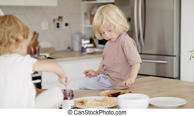 Young mother with two small children indoors in kitchen, eating pancakes.