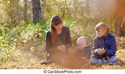 Young mother with two young children resting in the autumn park on a sunny day