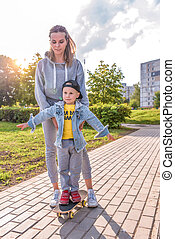 Young mother woman teaches skateboarding to play with little boy 3-5 years old, education support, summer in city park, autumn clothes on nature, emotions of tenderness love and care.