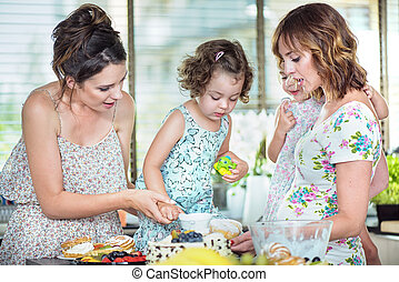 Young mothers making a cake with their daughters
