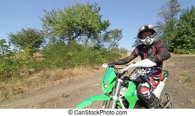 Young motocross racer sitting of his dirt bike looking away