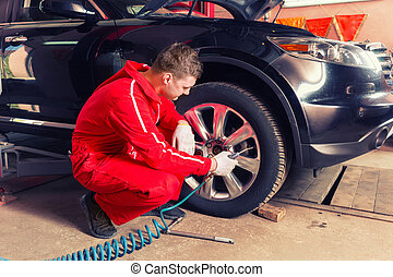 Young motor mechanic is going to check the air pressure
