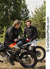 Young motorcyclists laughing in forest
