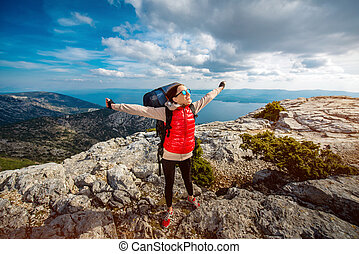 Young mountain climber on the top of island - Young woman...