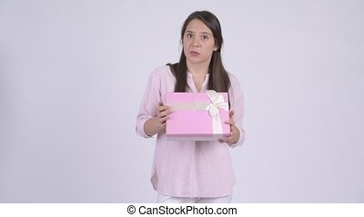 Young multi-ethnic businesswoman thinking while holding gift box