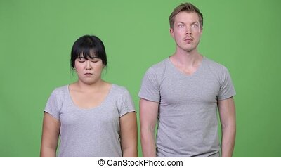 Young multi-ethnic couple looking at opposite directions...