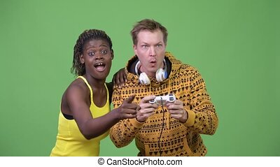 Young multi-ethnic couple playing games together - Studio...