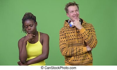 Young multi-ethnic couple thinking together - Studio shot of...