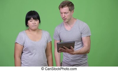 Young multi-ethnic couple using digital tablet and getting bad news together