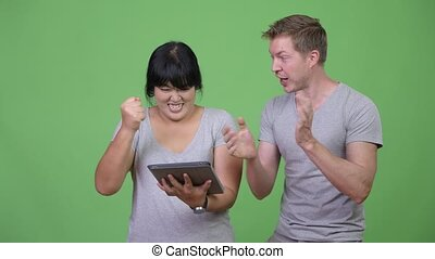 Young multi-ethnic couple using digital tablet and getting good news together