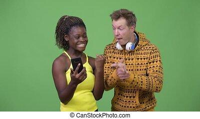 Young multi-ethnic couple using phone together - Studio shot...