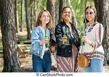Young multi-ethnic girls drinking at campsite - Portrait of ...