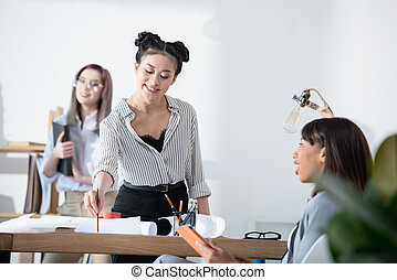 young multiethnic businesswomen in formal wear working at office together