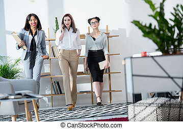 young multiethnic businesswomen walking at office together