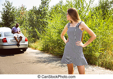 Young multiethnic international couple traveling on the car in sunny day