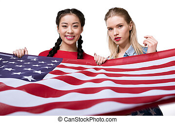 young multiethnic women looking at camera and holding flag of USA isolated on white, Independence Day Celebration