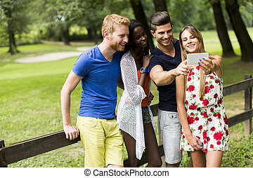 Young multiracial friends taking selfie in the park