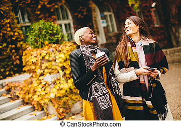 Young multiracial friends walking around the town