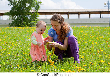 Young mum with a small daughter play to a glade with dandelions