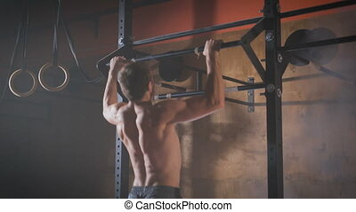 Young muscular athlete doing pull-up exercises.