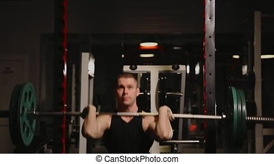Young muscular man at the gym performing squats.