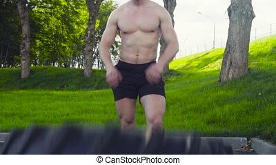 Young muscular man doing crossfit exercises outdoors