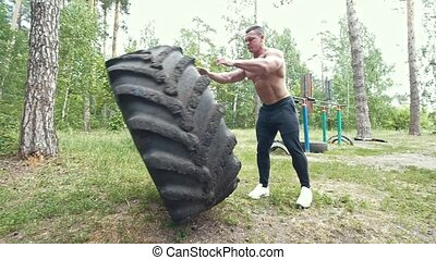 Young muscular man doing exercises workout lifting a huge rubber wheel in the forest