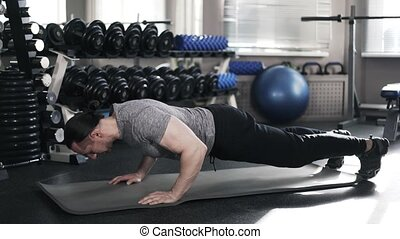 Young muscular man doing push ups in a gym
