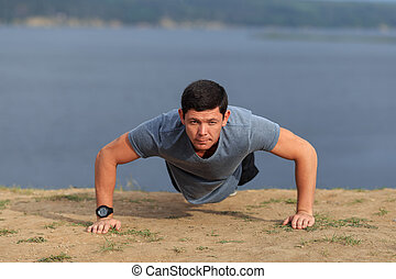 young muscular man doing push-ups outdoors