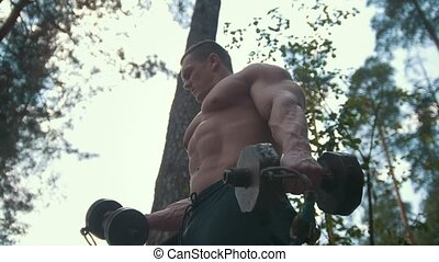 Young muscular man engaged with heavy iron dumbbells in the forest