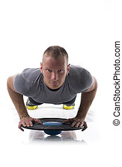 Young muscular man exercising on the floor with balance disc board