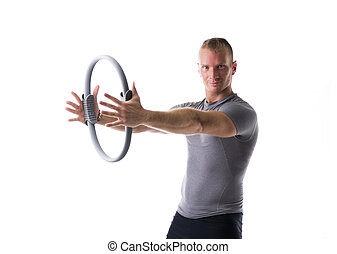 Young muscular man exercising with Pilates ring
