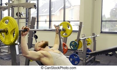 Young muscular man in gym lifting a barbell on bench.