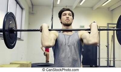 Young muscular man in gym lifting heavy barbell