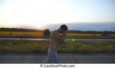 Young muscular man jogging in country road at sunset. Profile of male jogger training for marathon run outdoor. Athlete exercising against blue sky with sun. Sport and active lifestyle. Slow motion