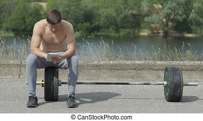 Young muscular man sitting after fitness training and using tablet computer